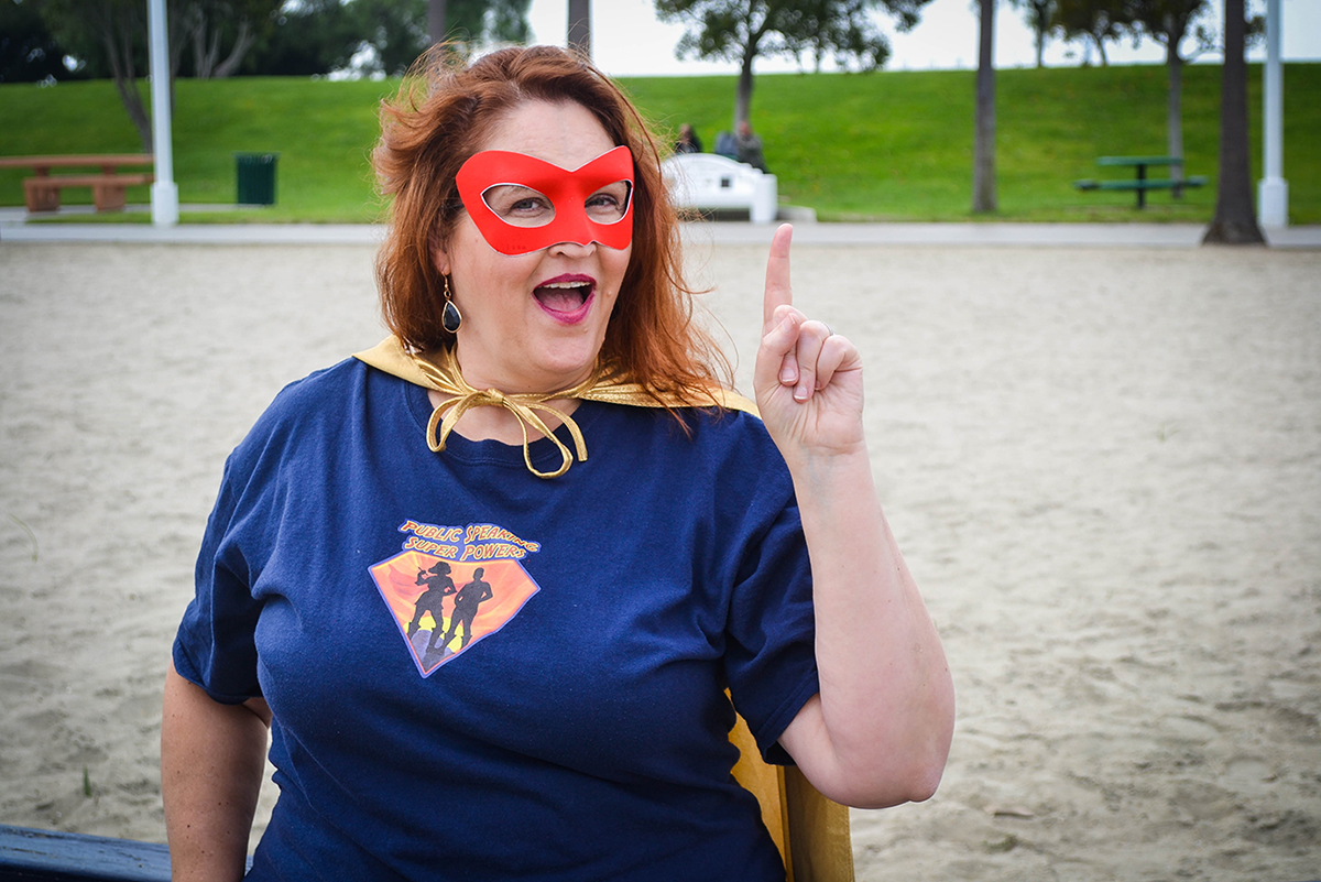 Carma Spence in a superhero outfit with an aha gesture